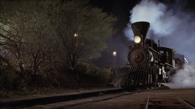 MEDIUM ANGLE OF PARKED STEAM ENGINE LOCOMOTIVE, OR TRAIN. SEE HEADLIGHTS ON. SEE SMOKE COMING FROM TRAIN. SEE TRAIN MOVE FORWARD. SEE TRAIN DRIVE RIGHT TO LEFT.