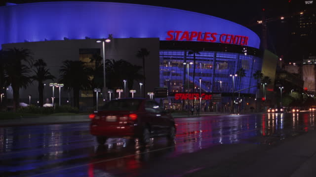 pan right to left as an suv car drives past the staples center basketball arena or stadium in downtown los angeles. also used as a concert hall or venue. the car also passes the convention center. - staples center stock videos and b-roll footage