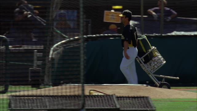 MEDIUM ANGLE OF BASEBALL PLAYER IN UNIFORM ROLLING CART OF BASEBALL ONTO FIELD AT OAKLAND ATHLETICS BASEBALL STADIUM. COULD BE PRACTICE.