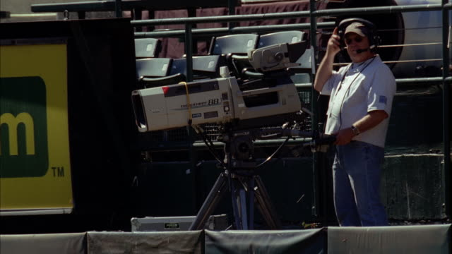 MEDIUM ANGLE OF CAMERAMAN WITH HEADSET AT OAKLAND ATHLETICS STADIUM.