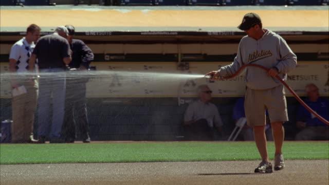 medium angle of maintenance men watering field at oakland athletics baseball stadium. - 芝草点の映像素材/bロール