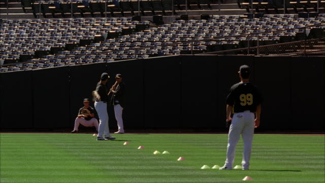 stockvideo's en b-roll-footage met medium angle of baseball players in uniform at oakland athletics baseball stadium. players throw or toss ball. could be practice. stadium seats visible. cones visible on field. - baseball uniform