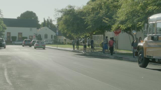 medium angle of children and pedestrian walking on suburban or neighborhood street. - männlicher teenager stock-videos und b-roll-filmmaterial