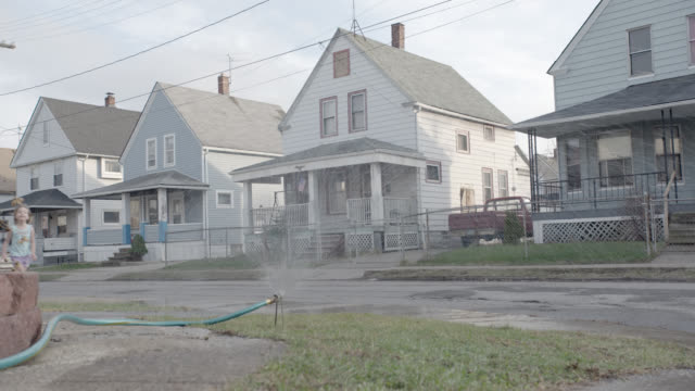 medium angle of two story lower class houses. children running through hose sprinkler on lawn. residential area or neighborhood. - neighbour stock videos and b-roll footage