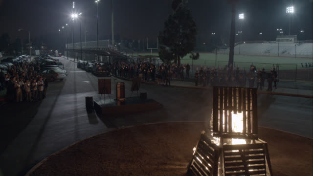 vídeos de stock, filmes e b-roll de wide angle of candlelight vigil in parking lot of high school football field or stadium. bonfire. crowds of students. - cerca
