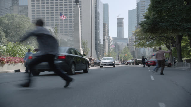 tracking shot of people running or fleeing on city street. could be attack or invasion. fire, explosions, and abandonded and overturned cars visible. newstruck visible. buildings and office buildings. - flüchten stock-videos und b-roll-filmmaterial