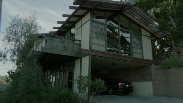 wide angle of car pulling into driveway of two story house. could be silverlake. - 引く点の映像素材/bロール