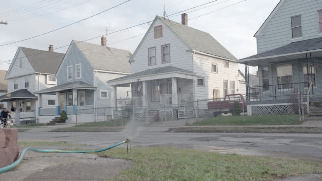 medium angle of two story lower class houses. hose sprinkler on lawn. residential area or neighborhood. - cleveland ohio stock videos and b-roll footage