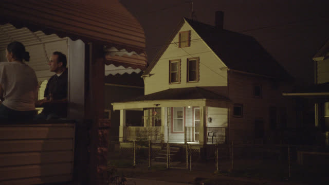 medium angle of lower class two story house. people in fg drinking beers on porch. - 玄関先点の映像素材/bロール