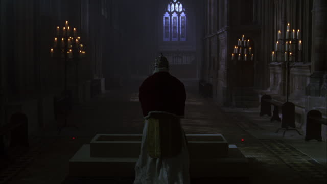 vidéos et rushes de zoom in to priest kneeling in prayer on altar in church or castle. pov moves forward as priest stands up and turns around to nod head. priest wears gold hat with jewelry decorations and red robe. medieval. middle ages. - prêtre