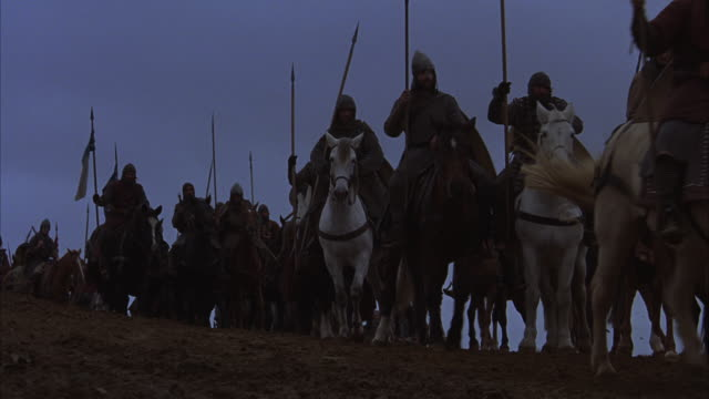 WIDE ANGLE OF KNIGHTS TRAVELING OVER DIRT HILL. KNIGHTS RIDE HORSEBACK AND OTHERS MARCH IN BG. KNIGHTS WEAR ARMOR AND CARRY FLAGS SHIELDS AND SPEARS. LARGE CROSS IS VISIBLE AT THE END OF THE PROCESSION. COULD BE USED FOR KNIGHTS GOING OFF TO FIGHT BATTLE.