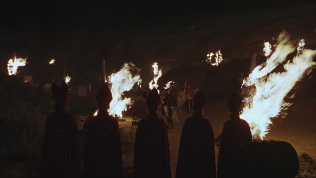 pan up five bishops or cardinals in red robes.  could be priests or other members of the clergy. they watch several knights or medieval soldiers burning people at the stake, swords and shields in hand.  could be used for a religious war, the crusades, or - medieval stock videos & royalty-free footage