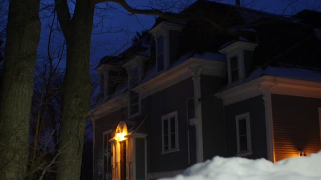 MEDIUM ANGLE OF MULTI-STORY VICTORIAN HOUSE. LIGHT OVER ENTRANCE AND SNOW VISIBLE IN YARD.