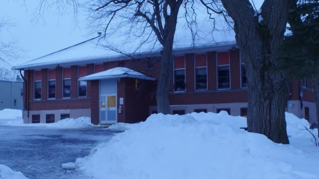 MEDIUM ANGLE OF TWO STORY BUILDING IN SNOW. COULD BE SCHOOL OR ASYLUM.