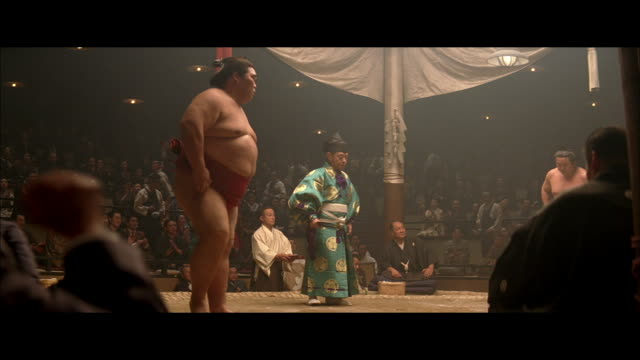 stockvideo's en b-roll-footage met medium angle of a sumo wrestling match in an arena or auditorium. raised ring is covered in clay and sand. crowd applauds as two wrestlers face off and perform pre match rituals of bowing, squatting, and tossing sand on ring. several men holding banners w - vasthouden