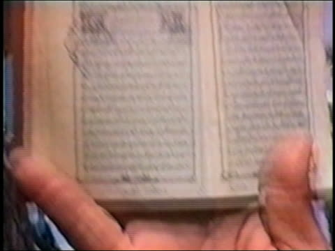 shaky from hand holding koran / medium shot al qaeda members / zoom in extreme close up hand holding koran / zoom out al qaeda - 2001 stock videos & royalty-free footage