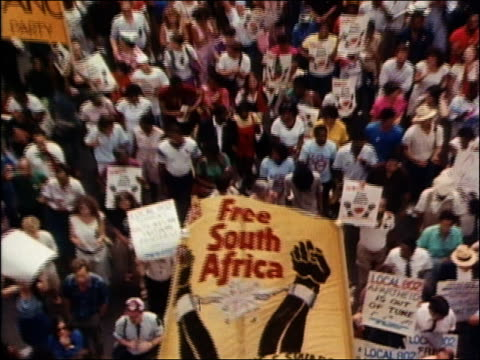 1980s high angle medium shot people holding Free South Africa banner in large demonstration / zoom out over crowd