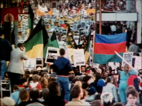 Wide shot crowd holding flags and banners at antiapartheid demonstration