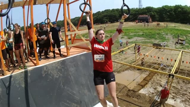 obstacle race point of view shot pov swinging on rings back and fourth to cross open pit - obstacle course stock videos & royalty-free footage