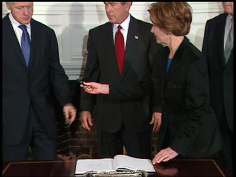 vídeos y material grabado en eventos de stock de medium shot zoom out laura bush and presidents clinton + bush signing tsunami condolence book/ audio/ washington - 2005