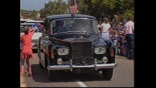 vídeos de stock e filmes b-roll de bairnsdale – royal motorcade down crowd lined street and doesn't stop – child throws bunch of flowers into royal car window as passes / paynesville... - 1985