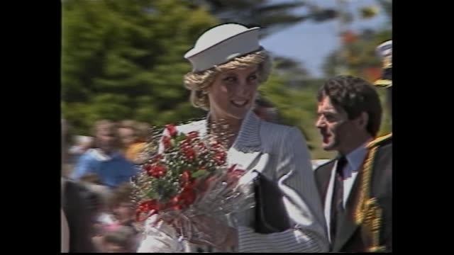 mass of school children waving flags / charles & di out of royal car / diana walks with flower posy -– smiles and waves / kids in colonial period... - 1985 stock-videos und b-roll-filmmaterial