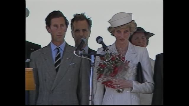princess diana wearing cream dress and sailer style hat walks holding posy of red flowers waves and– walks towards podium / on podium with prince... - 1985年点の映像素材/bロール