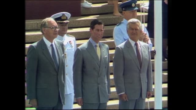 WIDE SHOT OFFICIAL PARTY ARRIVES AT DIAS / THREE SHOT GOVERNOR GENERAL SIR NINIAN STEPHEN PRINCE CHARLES PRIME MINISTER BOB HAWKE / ROYAL SALUTE – VS...