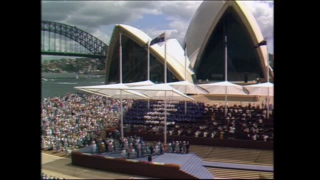 royal party stand to attention for long version of whole national anthem / close up flag in front of the opera house zoom out to see harbour bridge... - charles bridge stock-videos und b-roll-filmmaterial
