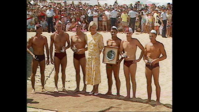 vídeos de stock, filmes e b-roll de princess diana meets surf life savers presents medals / shy diana photo op with life savers wearing speedo swimmers - calções de corrida