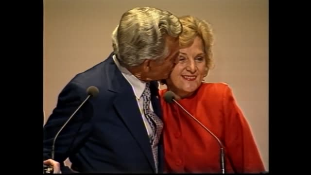 andrew peacock walks surrounded by media / prime minster bob hawke and hazel to podium / peacock presser smiling / hawke hugs hazel and kisses on... - cheek to cheek stock videos & royalty-free footage