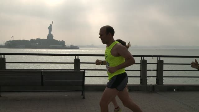 along ny harbor runners with statue of liberty in background - salmini stock videos and b-roll footage
