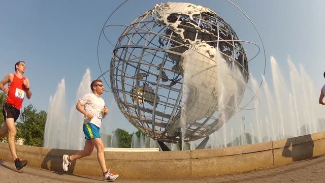 unisphere with fountains going runners go by - salmini stock videos and b-roll footage