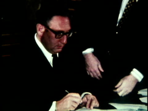 henry kissinger and vietnamese offcials signing the paris peace accord at the hotel magestic in paris / france - frieden stock-videos und b-roll-filmmaterial