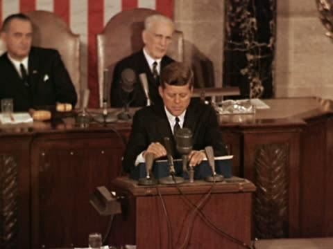 1960s medium shot JFK giving a speech to the House with LBJ and Speaker John McCormack in background / Washington DC