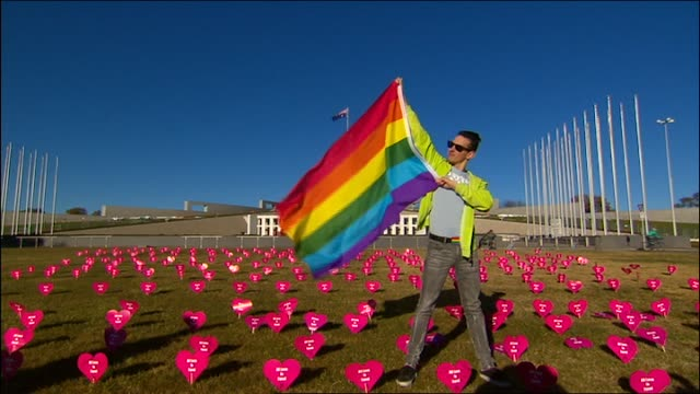 file vs man poses with rainbow pride flag at parliament house / vs same sex marriage rally march all love is equal sign held by man who then kisses... - parlamentsgebäude regierungsgebäude stock-videos und b-roll-filmmaterial