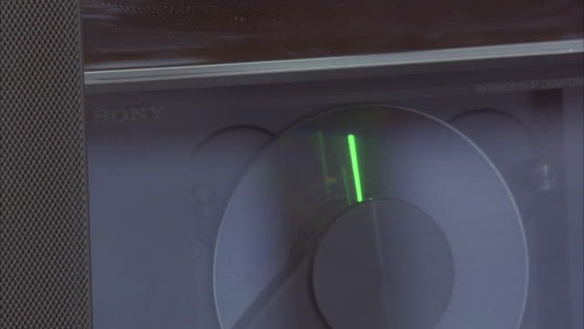 EST CLOSE ANGLE OF SPINNING CD IN CD PLAYER. SEE SONY LOGO ON CD PLAYER.