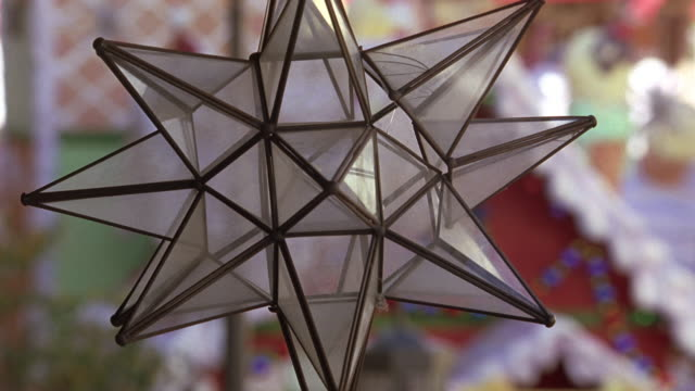 close angle of a christmas star christmas decoration.  a red house decorated red and white in the background. actual location the grove - 189 the grove drive, fairfax, los angeles. - the grove los angeles stock videos & royalty-free footage