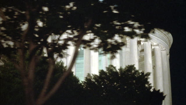 MEDIUM ANGLE PAN RIGHT OF JEFFERSON MEMORIAL LIT FROM INTERIOR AT NIGHT.
