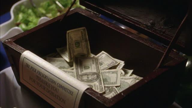 close angle of a wooden box filled with cash money.  sign on the box reads the pier preservation committee thanks you for your donation. charity, donations, fundraising, currency. - donation box stock videos & royalty-free footage