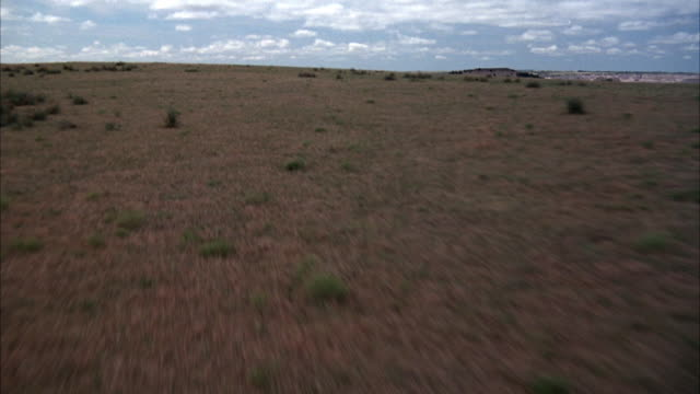 aerial in badlands national park, goes over grass on plains area. - バッドランズ国立公園点の映像素材/bロール