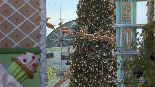 hand held angle panning down christmas decorations. several reindeer, a christmas star, and a christmas tree. a large spinning sign reads grove. actual location the grove - 189 the grove drive, fairfax, los angeles. - the grove los angeles stock videos & royalty-free footage