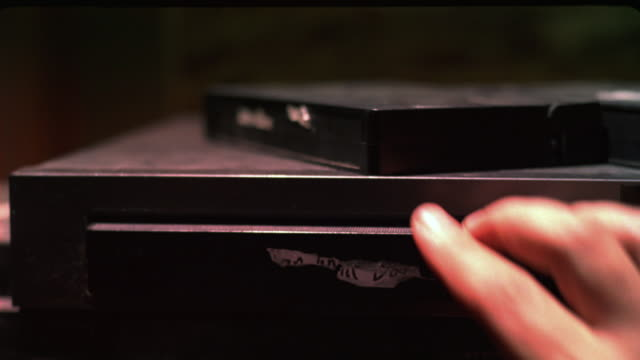 close angle of vcr with dusty video tapes stacked on top. a hand grabs a tape ejected from the vcr, places it on top, and inserts another tape. - inserting stock videos & royalty-free footage