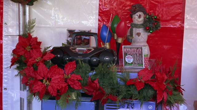 MEDIUM ANGLE OF A CD PLAYER, STEREO, OR BOOM BOX SURROUNDED BY CHRISTMAS DECORATIONS.  RED FLOWERS, PROBABLY POINSETTIAS, CANDY CANES, AND A POSTER OF A SNOW MAN. ACTUAL LOCATION THE GROVE - 189 THE GROVE DRIVE, FAIRFAX, LOS ANGELES.