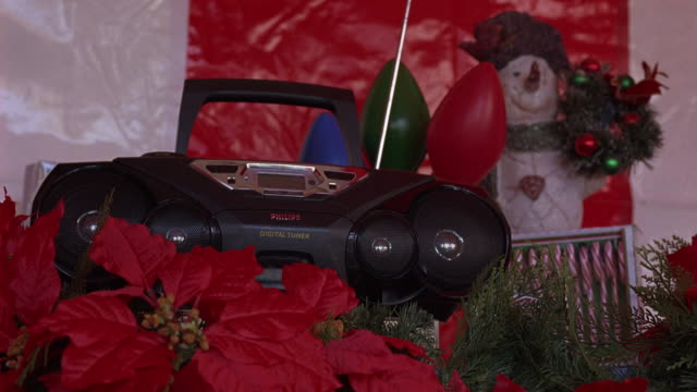 close angle of a cd player, stereo, or boom box surrounded by christmas decorations.  red flowers, probably poinsettias, candy canes, and a poster of a snow man. - compact disc player stock videos & royalty-free footage
