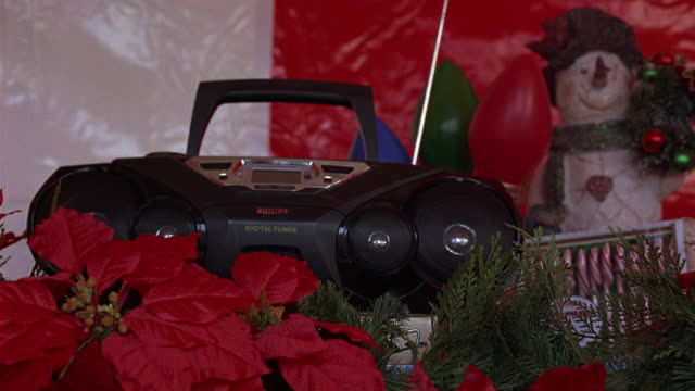 CLOSE ANGLE OF A CD PLAYER, STEREO, OR BOOM BOX SURROUNDED BY CHRISTMAS DECORATIONS.  RED FLOWERS, PROBABLY POINSETTIAS, CANDY CANES, AND A POSTER OF A SNOW MAN.
