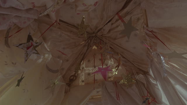 up angle of a mobile of stars hanging from a canopy on a baby's crib or a child's fort. the camera shakes up and down.  could be used as a baby pov. - hanging mobile stock videos & royalty-free footage