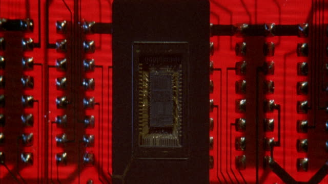 close angle of circuitry board. see panels of circuits surrounding what could be main computer chip on board. circuit colors change from red to white then to multicolors. neg. cut. - computer chip stock videos & royalty-free footage