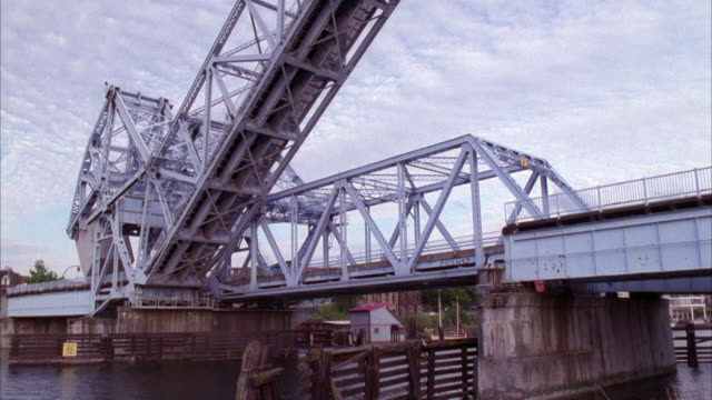 vídeos de stock, filmes e b-roll de medium angle of drawbridge unfolding and folding. drawbridge unfold at end. see river below bridge. - drawbridge