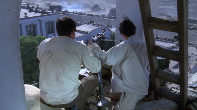 medium angle of two men firing machine gun from elevated position in mexican fort. men have white shirts on. see ladder on right leading to higher position. see rest of fort in background. battle scene. action. - automatic stock videos & royalty-free footage